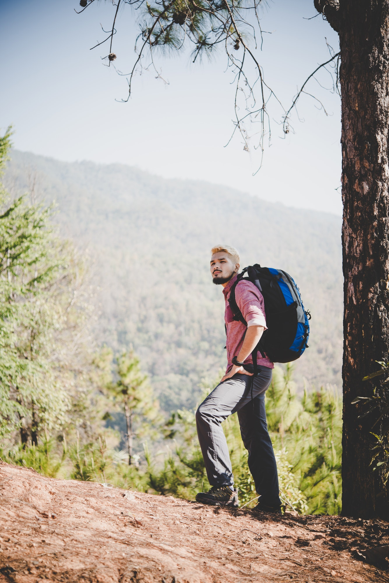 Hiker with big traveling backpack traveling to the mountain.